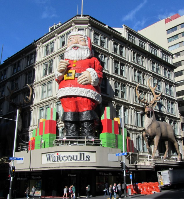 Santa with his reindeer and presents on top of Whitcoulls Building cnr of Queen & Victoria Sts