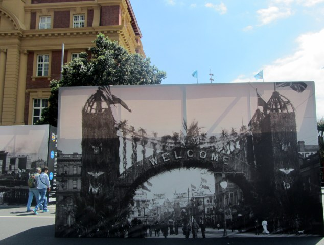 Photo billboard depicting the arch and decorations on Lower Queen St in 1908